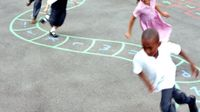 Kids running through a pathway drawn with chalk on the playground