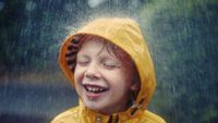 A young boy in a yellow rain coat is smiling with his eyes closed, and rain is pouring down on him.