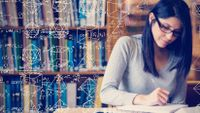 Photo of a female student studying math, with equations and geometric shapes drawn in white on the image