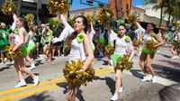 A street parade is going on in a downtown area. A lot of girls in white shirts and green shorts are walking in the street with their hands raised, carrying golden pom-poms.
