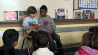 Two primary students are reading in front of the classroom