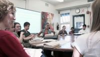 Senior students are sitting around a round table. They are having a discussion.