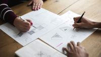 Two students work on geometric illustrations.