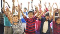 Children in a classroom raise both hands in the air during a movement break.