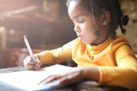 Profile of little girl writing at home.