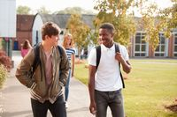 Two high school students walking together on campus, smiling
