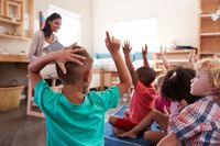 Students raising their hands in a kindergarten class