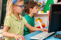 Two elementary students playing videogames on PCs