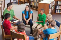 A group of middle school students gathered in chairs in a circle, talking out an issue with an adult