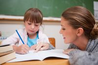 Teacher observing a young student as she writes in a notebook in class