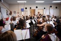 A middle school music class of bowed instrument players, all raising their bows in the air before playing