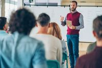A teacher gesturing in front of a whiteboard to a room of his fellow teachers and faculty