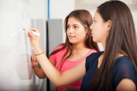 Two high school girls doing math equations on the whiteboard