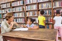 A librarian talking to a young girl at a table while two students browse the stacks behind them