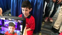 A young boy being filmed on a tablet for a video