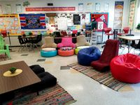 A flexible classroom with colorful, chairs, tables, carpets, and posters