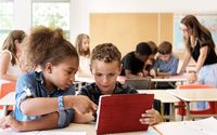 A classroom full of kids using tablets. The teacher is helping a group in the background and two students are working together in the foreground.
