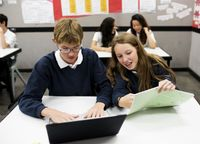 Students working in pairs together with laptops and handouts in class