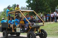 Teacher Brian Copes and his students riding together in a golf cart they modified