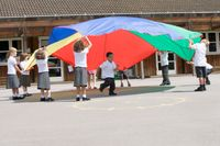 A group of elementary students playing with a colorful parachute during PE