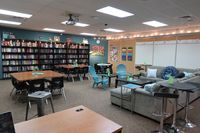 A flexible classroom with desks, tables, a couch, and big bookcases