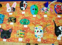A table covered in student-made papier-mâché masks