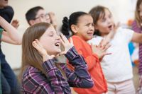 A class of elementary drama students make a variety of pronounced expressions