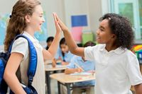 Two elementary students high-fiving in a classroom