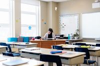 A teacher sitting alone in an empty classroom, grading papers