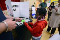 "An elementary school girl submitting a mock election ballot in a school gym and receiving an ""I Voted"" sticker from a teacher"