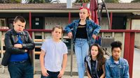 A group of five students wearing greaser outfits, posing outside of their school