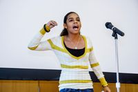 A teenage girl performing spoken word poetry in front of a microphone in a school assembly room