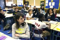 A classroom full of diverse high school students sitting at their desks, looking toward the front of the room