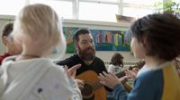 A teacher playing guitar for young elementary students