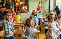Elementary students jumping and playing in a classroom