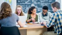 Diverse high school students studying together in class
