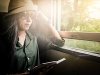 A woman in sunglasses and a hat sitting on a train on a sunny day with the window cracked open, reading a book