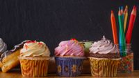 An array of cupcakes and doughnuts sitting in front of a classroom blackboard and a jar of colored pencils