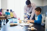 teacher helping hispanic student with science project