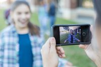 Photograph of a student recording another student with a smart phone.