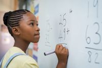 Student working on math problems at a white board