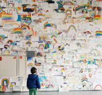 Young child looking at wall covered in rainbow drawings