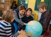Teacher and students looking at a globe
