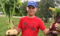 Student holding harvested vegetables while participating in a gardening project through Cabot Leads program.