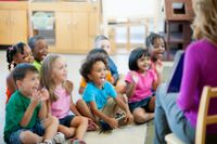 Pre-K students sitting on the floor listening to their teacher