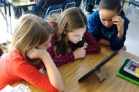 Three middle school students working on a tablet together