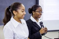 Two female middle school students dressed in business attire giving a presentation at a podium