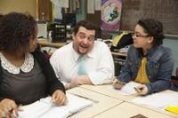 High School teacher kneeling down to talk to 2 students sitting at their desks