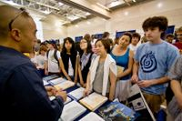 Students and parents listen to a college recruiter at a college fair