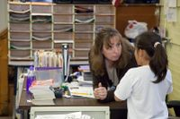 Teacher bending over talking to elementary student